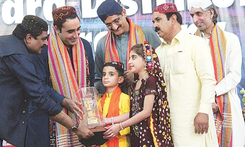 PPP chairman Bilawal Bhutto-Zardari gives away the Latif Award to master Intikhab Burdi and Baby Rahat Burdi at the closing session of the urs on Monday. The children have incredibly memorised a big volume of Shah Bhitai's poetry.—PPI