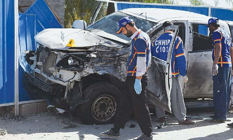 VOLUNTEERS examine the vehicle of the police officer at the site of the suicide attack on Thursday.—AFP