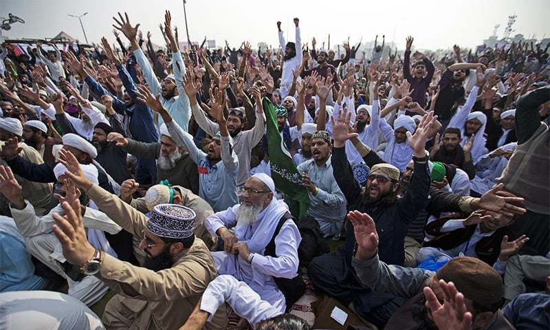 Protesters belonging to religious parties shout slogans during a sit-in in Islamabad on Friday. ─ AP
