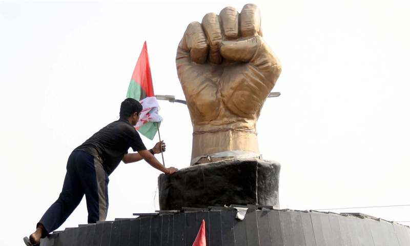 MQM worker hoists a party flag ahead of the arrival of MQM chief Dr Farooq Sattar at martyrs memorial in Azizabad. —Online