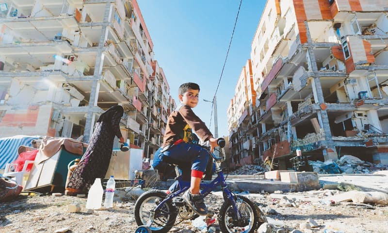 A BOY rides a bicycle through the rubble near damaged buildings in the town of Sarpol-e Zahab, Kermanshah province, on Tuesday.—AFP