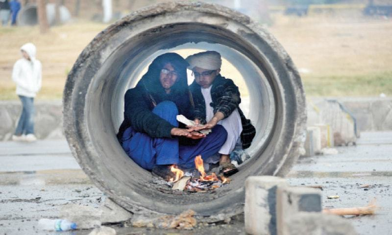 Two protesters sit inside a sewerage pipeline to keep themselves warm following rain on Tuesday. — Photo by Mohammad Asim