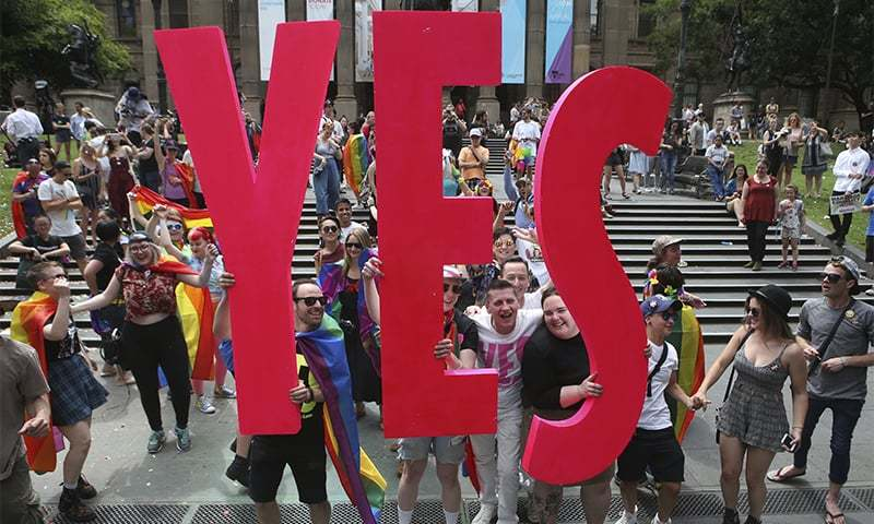 People celebrate after the announcement of the same-sex marriage postal survey result in front of the State Library of Victoria in Melbourne ─ AP