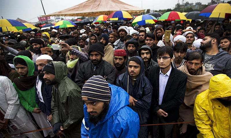 Supporters of religious parties listen to their leaders during a sit-in protest in Islamabad. ─ AP