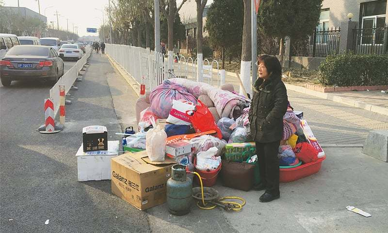 Beijing: A resident stands next to her belongings along a road after being evacuated following a fatal housing block fire on Sunday.—AFP