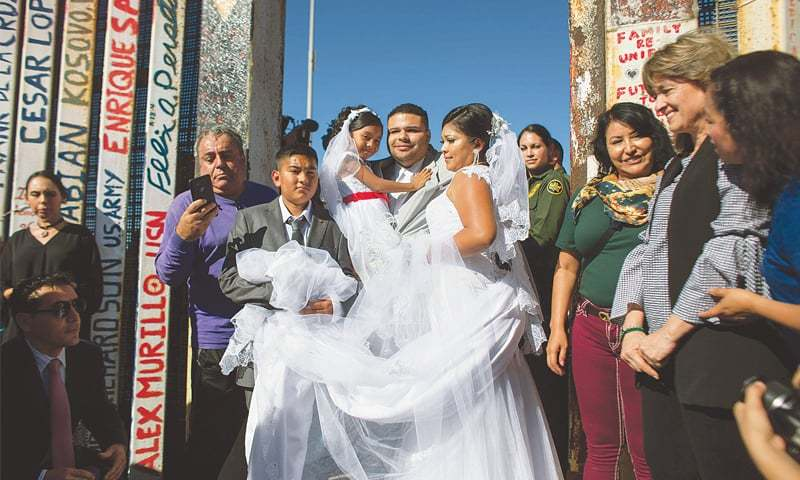 "Bride Evelia Reyes and groom Brian Houston, living on different sides of the US-Mexico border, stand for a family portrait after getting married during a brief reunion during the ""Opening the Door of Hope"" event at the border fence gate in Playas de Tijuana, Mexico, on Saturday.—AFP"