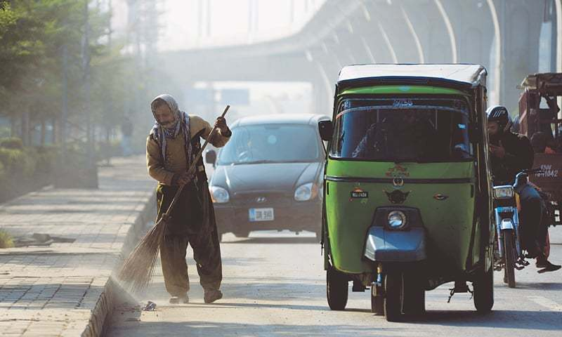 A SANITARY worker sweeps up a section of Murree Road in full rush-hour traffic.—Mohammad Asim / White Star