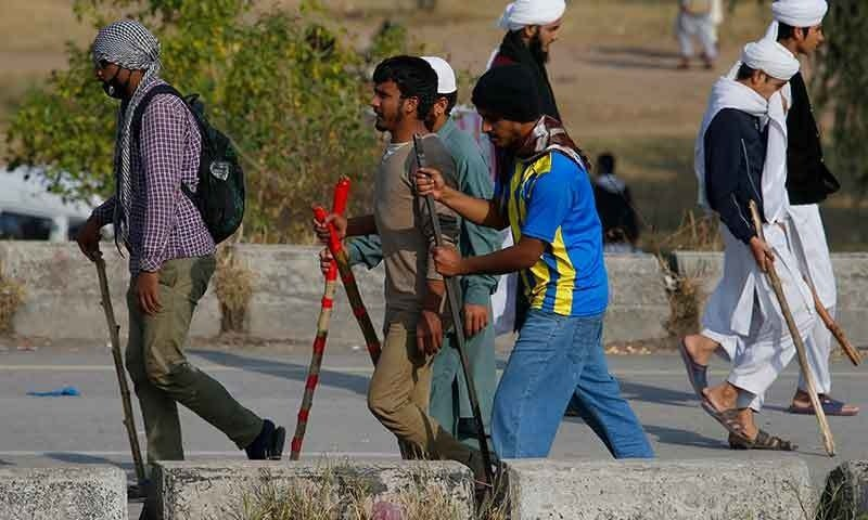 Protesters armed with sticks patrol close to the site of the protest in Islamabad. Photo: AP