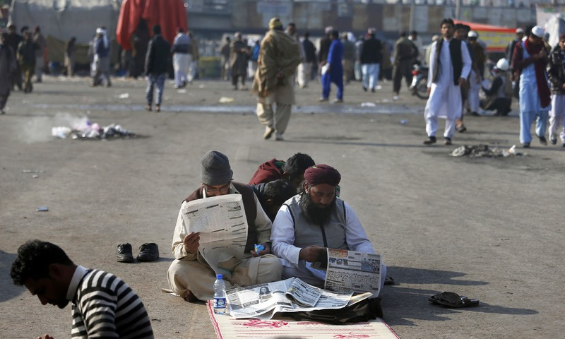 Supporters of religious parties read newspapers during a sit-in protest at Faizabad. —AP