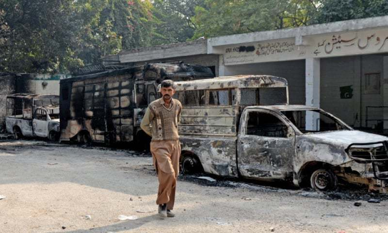 A man walks past charred remains of police vehicles at Faizabad on Sunday. — Photo by Mohammad Asim