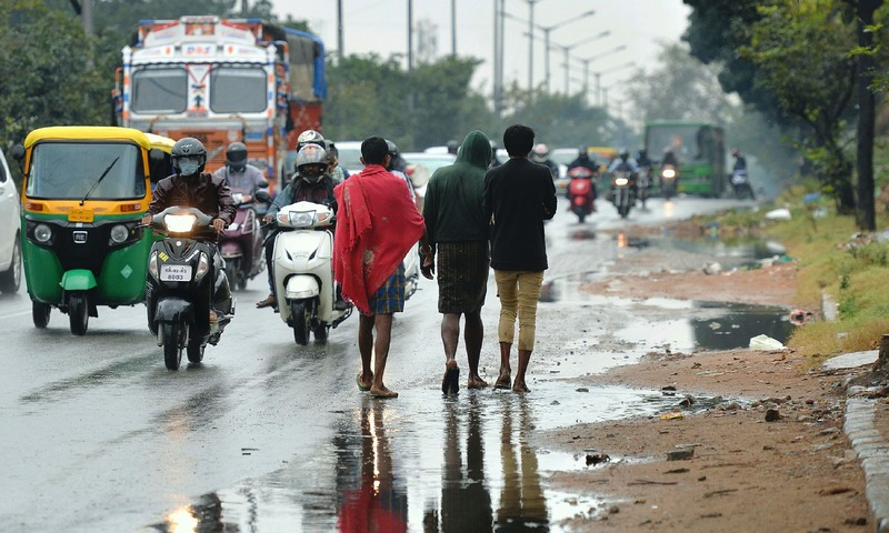Indian pedestrians walk on the road after copious rains in Bangalore on December 1, 2017. —AFP