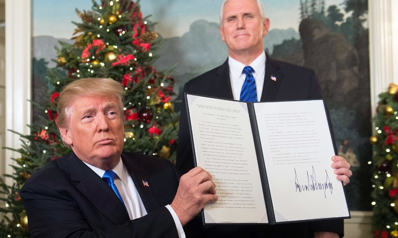 US President Donald Trump holds up a signed memorandum after he delivered a statement on Jerusalem. —AFP