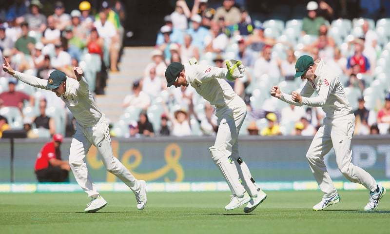 ADELAIDE: Australian captain Steve Smith (L), wicket-keeper Tim Paine (C) and Peter Handscomb celebrate the fall of the last English wicket during the second Ashes Test at the Adelaide Oval on Wednesday.—AP