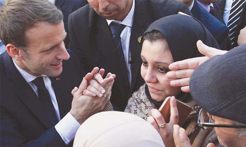 ALGIERS: French President Emmanuel Macron holds the hands of a woman as he meets residents on Wednesday.—AP
