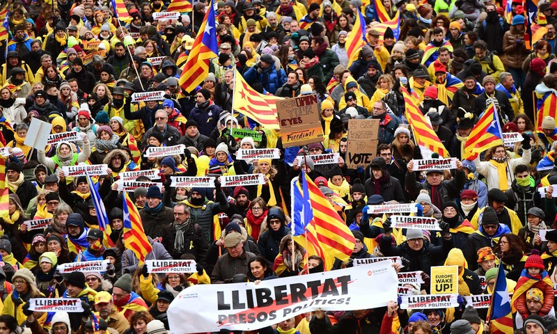 People wave Catalan 'Estelada' flags and carry signs during a pro-independence demonstration on December 7, 2017 in Brussels. —AFP