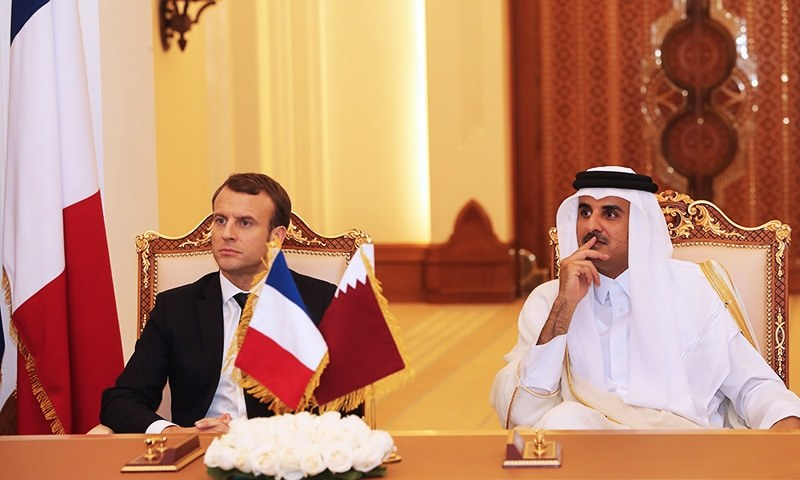 French President Emmanuel Macron and Qatari Emir Sheikh Tamim bin Hamad al-Thani watch as their foreign ministers sign bilateral agreements in the Qatari capital Doha.—AFP