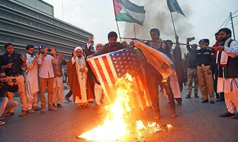 مجلس وحدت المسلیمن کے کارکنوں نے ایم ٹی خان روڑ پر امریکی اور اسرائیلی پرچم نذر آتش کیے—فوٹو:اے ایف پی