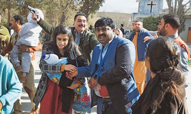 QUETTA: A family is being evacuated from the church premises after the attack.—AFP