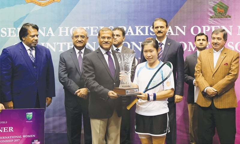 ISLAMABAD: Hong Kong's Annie Au receives the CAS International Women's Squash Championship trophy from Chief of Air Staff Air Chief Marshal Sohail Aman at the Mushaf Sports Complex on Friday. Squash legends Jahangir Khan (L) and Qamar Zaman (R) are also seen.—Courtesy PSF