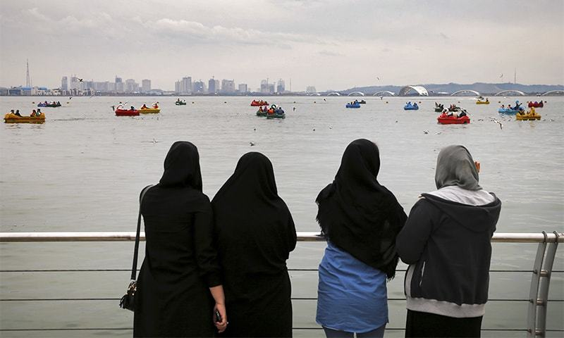 Women watch people riding boats on the Persian Gulf Martyrs lake during the ancient festival of Sizdeh Bedar, an annual public picnic day on the 13th day of the Iranian new year, west of Tehran, Iran.— AP/File