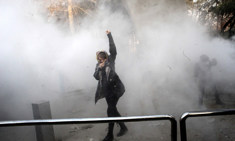 An Iranian woman raises her fist amid the smoke of tear gas at the University of Tehran during a protest driven by anger over economic problems, in the capital Tehran on December 30, 2017. —AFP