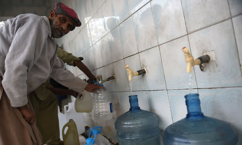 A man filling bottles at a water filtration plant in Islamabad. — AFP