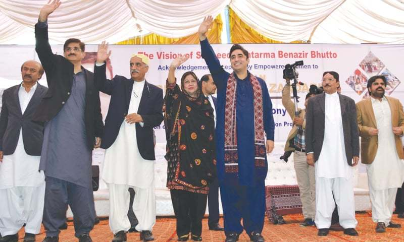 Bilawal Bhutto-Zardari and other PPP leaders wave to the audience at the ceremony in Sukkur on Monday.—Dawn
