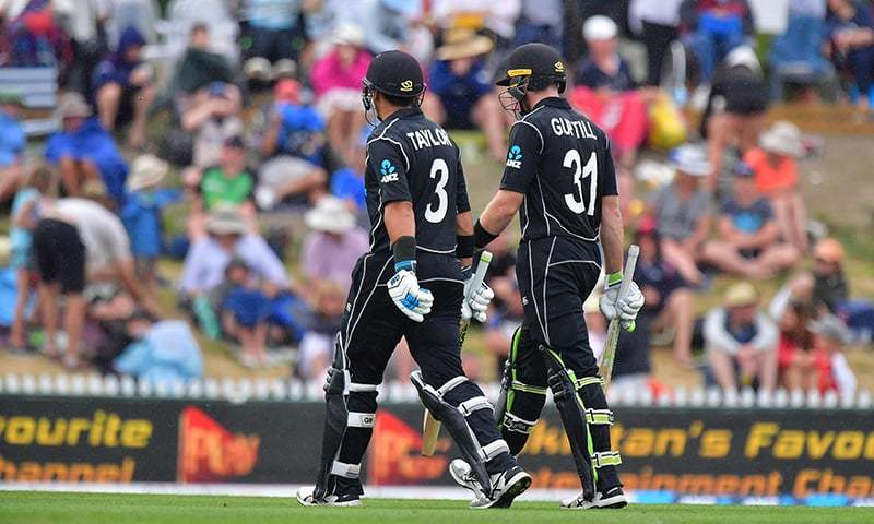 New Zealand's Martin Guptill (R) and Ross Taylor walk from the field as the rain falls during the second ODI between New Zealand and Pakistan. — AFP