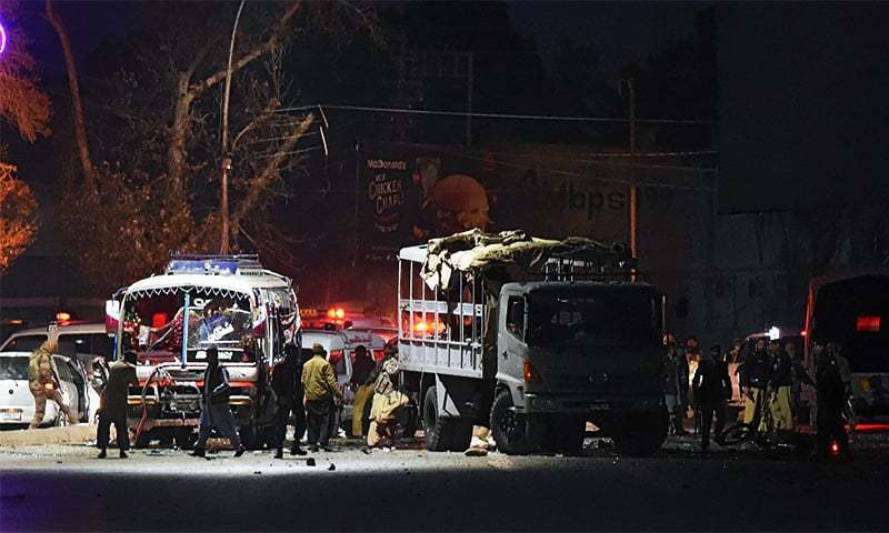 Security officials gather around a damaged police bus at the site of a suicide bomb attack in Quetta.— AFP
