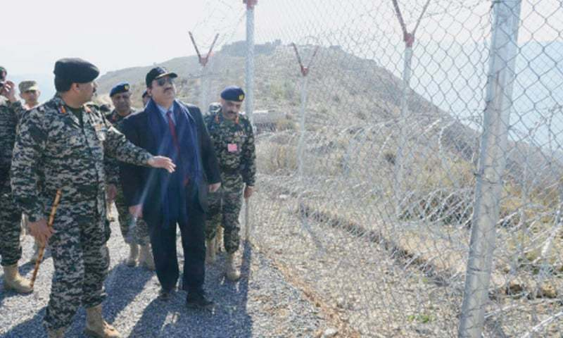 ALONG THE PAK-AFGHAN BORDER: Defence Minister Khurram Dastagir Khan is being briefed on Wednesday about the work being carried out to erect a fence aimed at stopping illegal crossing of the border, during a visit to Khyber Agency.—Online