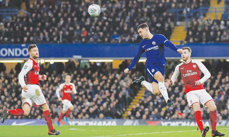 LONDON: Chelsea's Eden Hazard (C) wins a header as Arsenal's Shkodran Mustafi (L) and Callum Chambers look on during the English League Cup semi-final first leg at Stamford Bridge.—AFP
