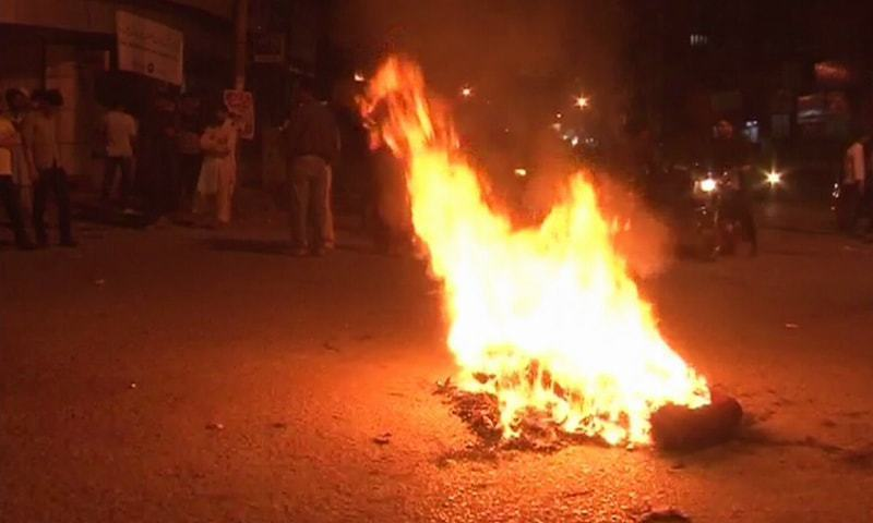 Residents burn tyres after a minor boy went missing on Burns Road.— DawnNews