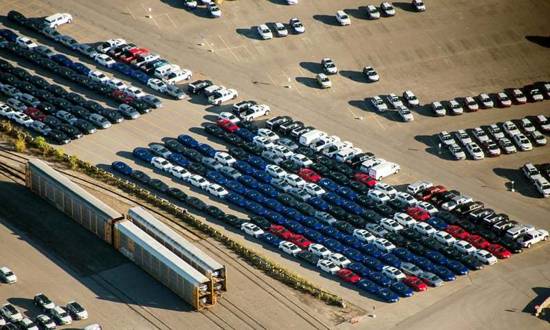 Toronto: Vehicles sit parked near freight trains in a rail yard in this aerial photograph.— Bloomberg