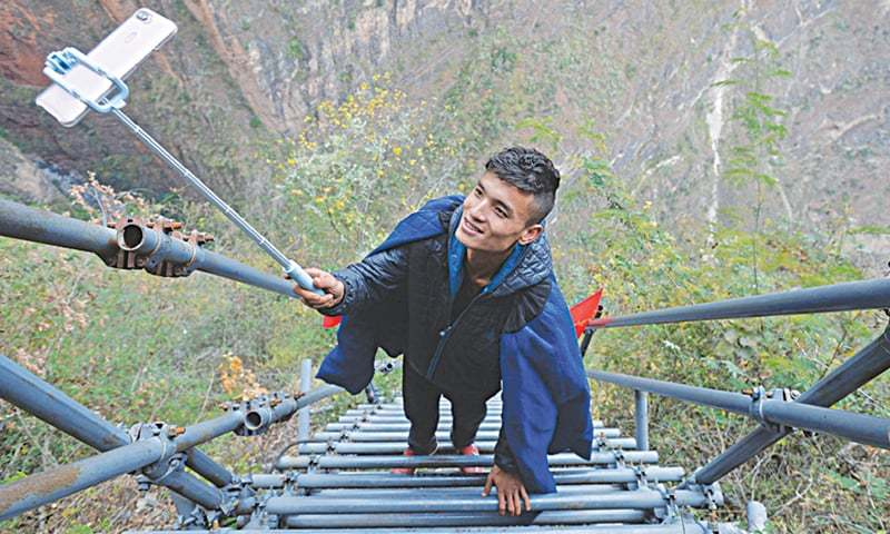 YANG Yang, a young man of the Yi ethnic group, broadcasts live climbing a steel ladder at Atuleer, a village in Zhaojue county, China, in this file picture taken in December.—China Daily
