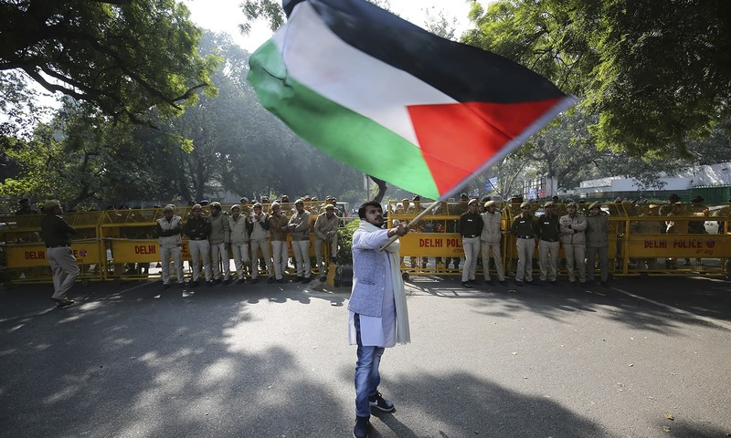 A protestor waves Palestinian flag as Indian police barricades a road during a protest by members of India's various left parties and civilians — AP