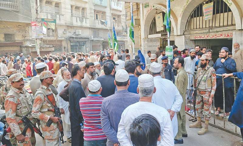 Rangers personnel and traders gather on the spot in the Kharadar cloth market, where a hand grenade was thrown by suspects on Thursday.—INP