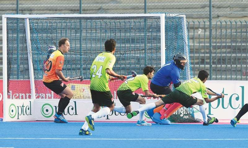 LAHORE: Players of Pakistan U-18 and World XI in action during the second exhibition match at the National Hockey Stadium on Sunday.—M.Arif/White Star