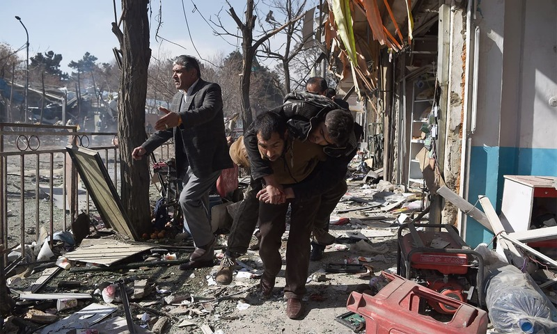 Afghan volunteers carry a body at the scene of a car bomb exploded in front of the old Ministry of Interior building in Kabul on Saturday.— AFP
