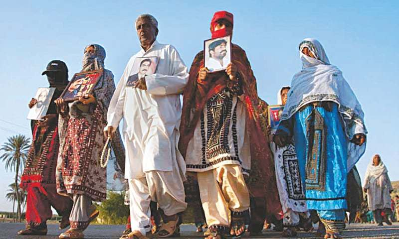 Baloch protestors march towards Karachi, holding photographs of their relatives who were allegedly abducted by security forces | AP/Dawn file photo