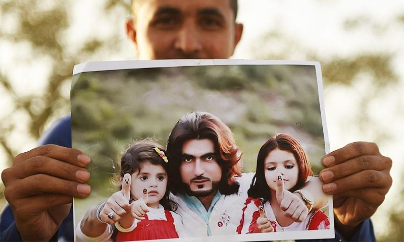 A protester holds a photograph of 23-year-old Naqeebullah Mehsud during a protest in Karachi.  ─ AFP