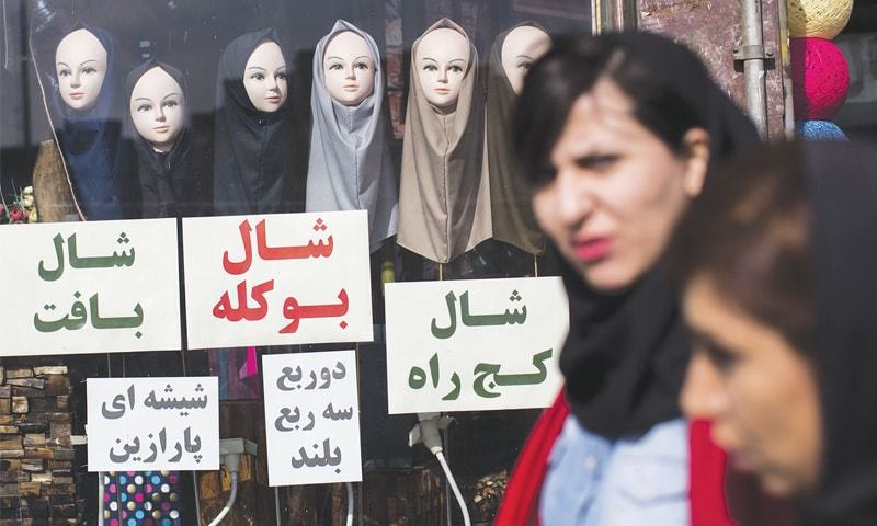 THIS file photo shows two Iranian women walking past a shop displaying scarves on mannequins in Tehran.—AFP