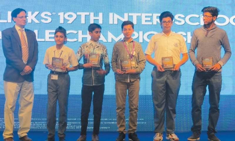 WINNERS of the 19th Inter-school Scrabble Championship — Hammad Hamid, Abdullah Ayub, Ali Wasif, Sulamena Mohiuddin and Ali Raza Pabany — seen with their prizes as tournament director Tariq Parvez looks on.