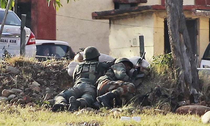 Indian soldiers take their positions surrounding the residential quarters where militants are believed to be holed up in an army camp in India-held Kashmir. ─ AP