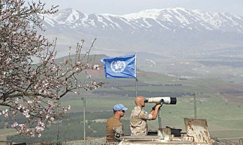 A UN peacekeeper looks through binoculars to monitor the Israel-Syria border in the Israeli-annexed Golan Heights.—AFP