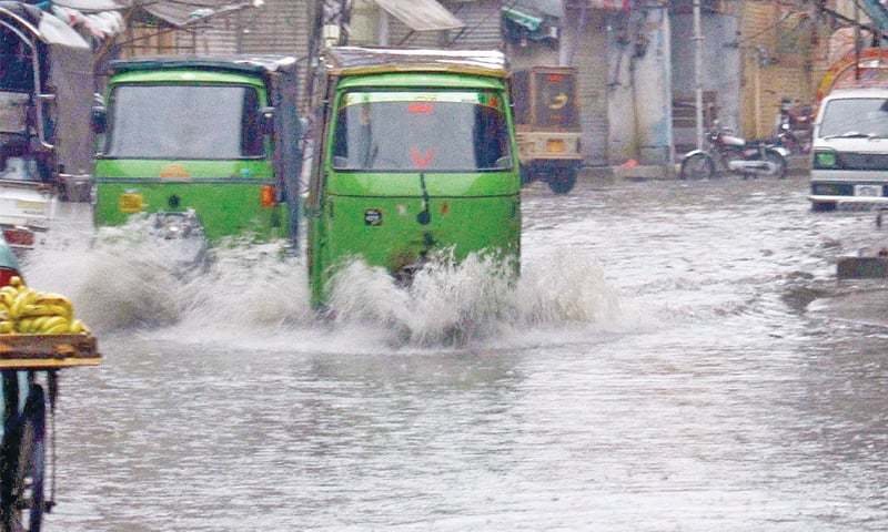 Rickshaws drive through rainwater that accumulated on a road in Rawalpindi following a downpour on Monday. — INP