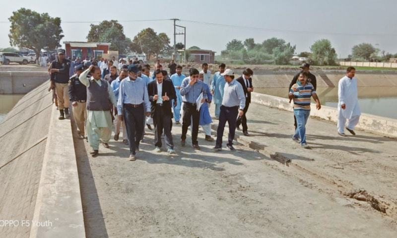 RETIRED Justice Amir Hani Muslim inspects a water reservoir and its installations in Tharparkar on Tuesday. Officials of relevant departments are accompanying him.—Dawn