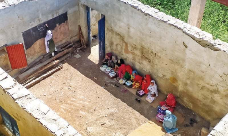 Students study in roofless classroom of a government primary school in Bishbanr. — Dawn