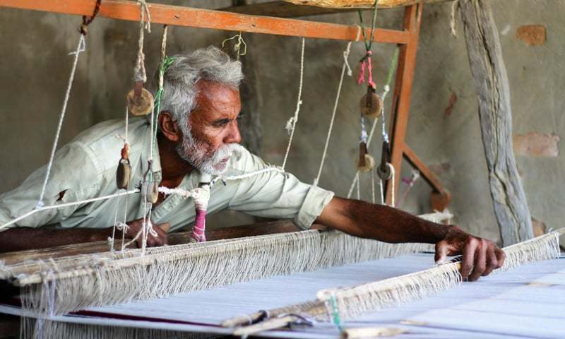 An old villager binds threads on the khaddi | Photos by the writer
