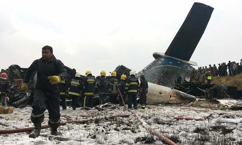 Nepalese Rescuers Stand Near A Passenger Plane From Bangladesh That Crashed At The Airport In Kathmandu