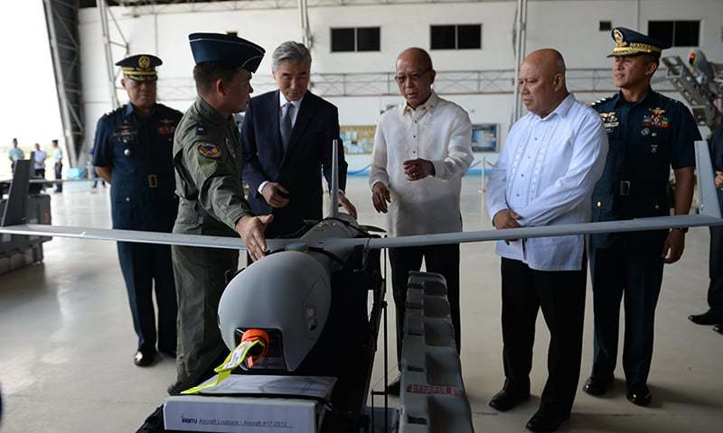 A Philippine airforce officer explains to US Ambassador to the Philippines Sung Y. Kim (3rd L) and Philippine Defense Secretary Delfin Lorenzana (3rd R) one of the six ScanEagle Unmanned Aerial Vehicles, at the military airbase in Manila on March 13, 2018. ─AFP